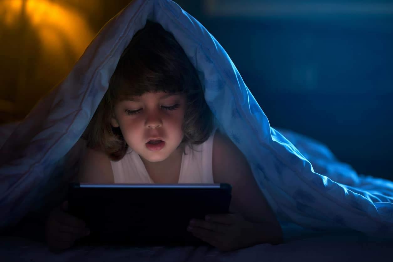 Little boy watching cartoons at night